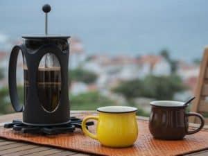 cafetera de émbolo y tazas de café