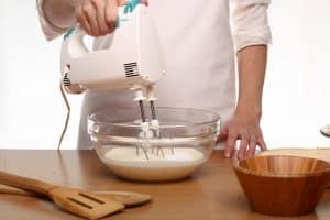 mujer usando una batidora de pastelería