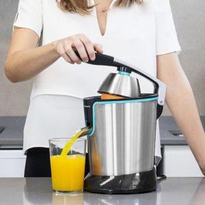 mujer usando un exprimidor de zumo