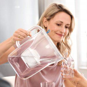 mujer con una jarra de agua filtrada