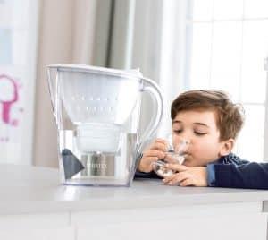 niño con una jarra de agua filtrada