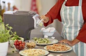 mujer haciendo pasta con una máquina para hacer pasta