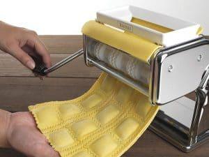 persona haciendo pasta con una máquina para hacer pasta