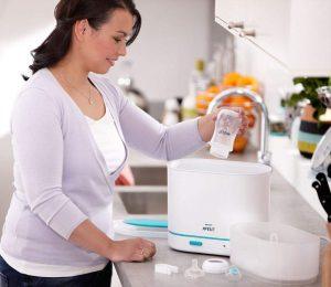 mujer usando un esterilizador eléctrico